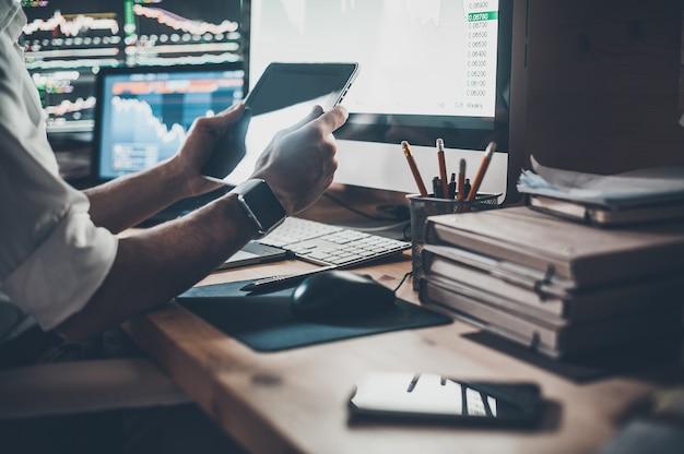 Utiliser les technologies modernes au travail. gros plan sur un jeune homme d'affaires tenant une tablette numérique alors qu'il était assis au bureau dans un bureau de création