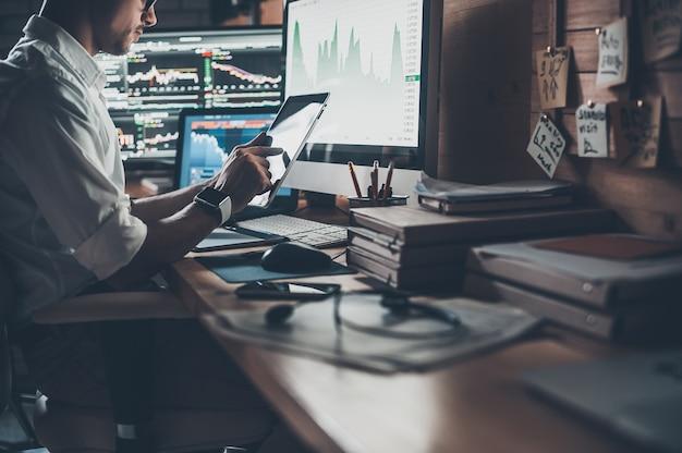 Utiliser les technologies modernes au travail. gros plan sur un jeune homme d'affaires travaillant sur une tablette numérique alors qu'il était assis au bureau dans un bureau de création