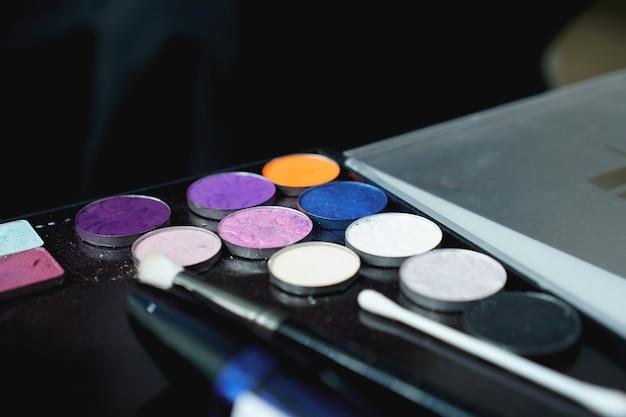 Utilisez la palette d'ombres pour le maquillage sur un arrière-plan flou, gros plan