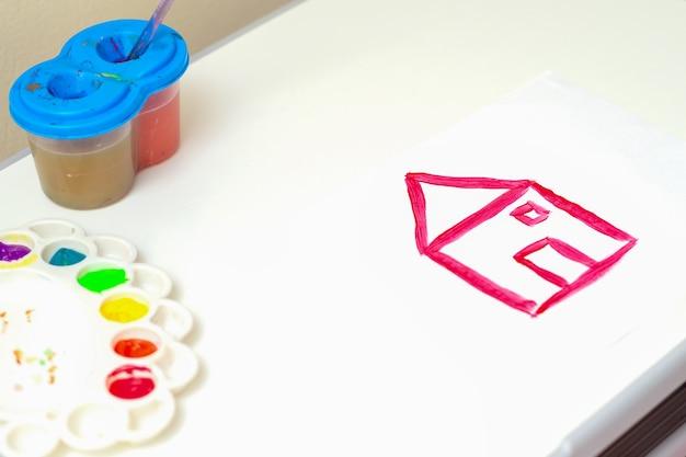 Uvres d'art pour enfants. dessin pour enfants d'une maison rouge simple à l'aquarelle sur une feuille de papier blanche.