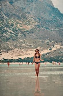 Vacances au bord de la mer. jolie jeune femme profitant de la vue sur la belle piscine rocheuse naturelle. le concept de voyage, de loisirs, de tourisme.