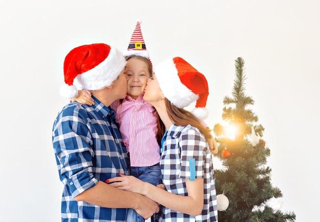 Vacances, cadeaux et concept d'arbre de noël - petite famille s'amusant ensemble à noël