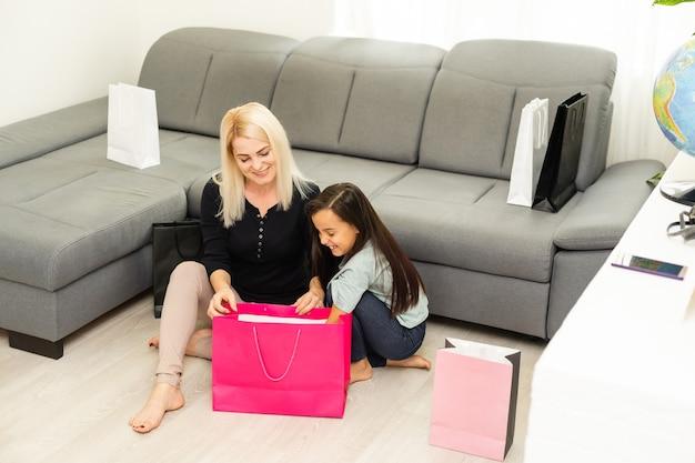 Vacances, cadeaux, noël, noël, concept d'anniversaire - heureuse mère et enfant fille avec des sacs-cadeaux