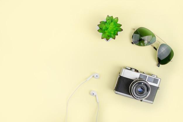 Vacances avec caméra argentique, lunettes de soleil sur fond jaune. vue de dessus.