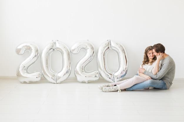 Vacances, concept festif et fête - couple d'amoureux heureux assis sur un sol près de ballons d'argent 2020. célébration du nouvel an