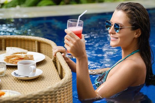 Vacances dans la station. jeune femme heureuse avec un petit déjeuner flottant dans la piscine.
