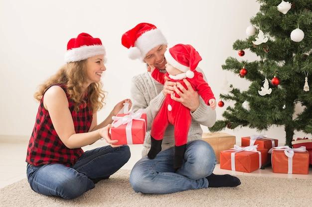 Vacances, enfants et concept de famille - couple heureux avec bébé célébrant noël ensemble à la maison.
