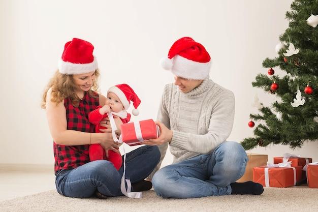 Vacances, Enfants Et Concept De Famille - Couple Heureux Avec Bébé Célébrant Noël Ensemble à La Maison. Photo Premium