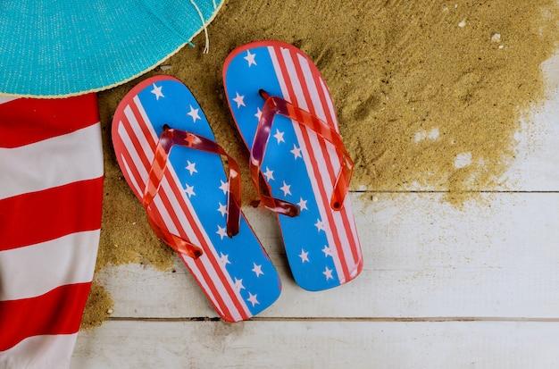 Vacances d'été avec des accessoires sur des tongs et un chapeau relaxant drapeau américain vue de dessus plat