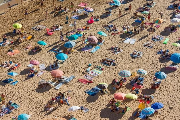 Vacances d'été au portugal. foule de baigneurs sur la plage de benagil en algarve
