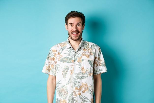 Vacances d'été. bel homme heureux en chemise hawaïenne à la recherche amusée, souriant à la caméra, debout sur fond bleu.