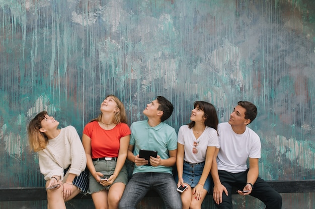 Vacances d'été et concept adolescent - groupe d'adolescents souriants qui traînent dehors.