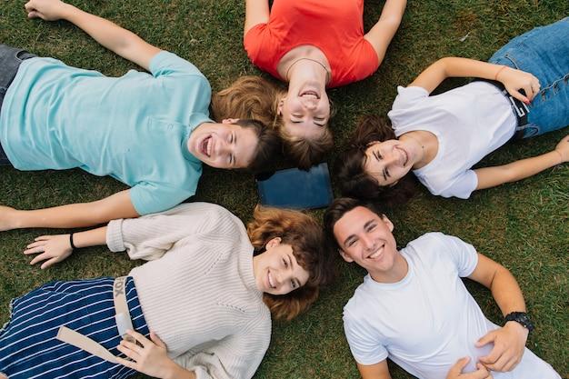 Vacances d'été et concept adolescent - groupe d'adolescents souriants avec tablette à l'extérieur.