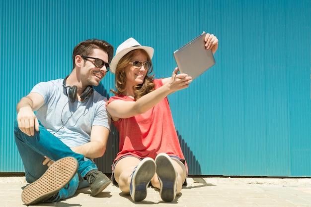 Vacances d'été, concept d'adolescent et de technologie - couple d'adolescents souriants dans des lunettes de soleil prenant un selfie avec un tablet pc