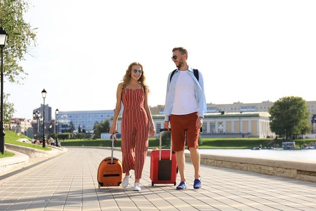 Vacances d'été, concept de tourisme - couple souriant avec bagages.