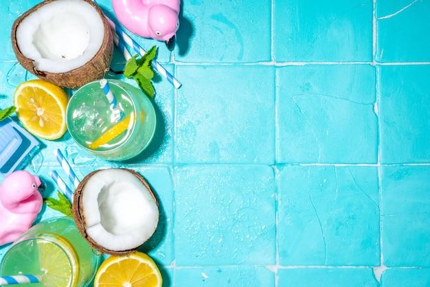 Vacances d'été ensoleillées et lumineuses. boisson à la limonade sur fond de carreaux de piscine bleus humides, avec accessoires de vacances à la plage, bouées de sauvetage flamants roses, citrons, noix de coco, menthe, feuilles tropicales, espace de copie vue de dessus flatlay