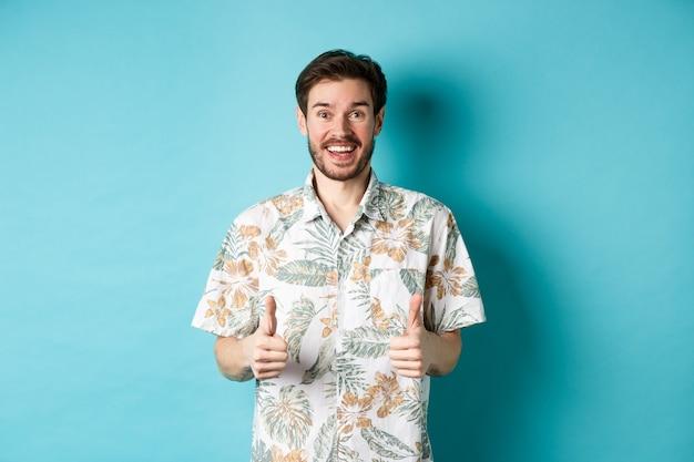 Vacances d'été. excité, touriste souriant en chemise hawaïenne, spectacle de pouce en l'air, louant un hôtel ou un lieu de vacances, debout sur fond bleu.