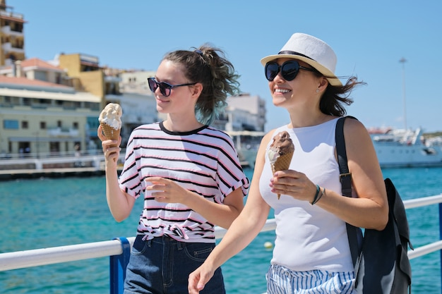 Vacances d'été en famille, mère et fille adolescent marchant ensemble manger des glaces