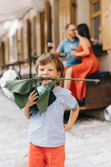 Vacances d'été en famille. le petit garçon au premier plan s'amuse et tient une fleur d'hortensia dans ses dents.