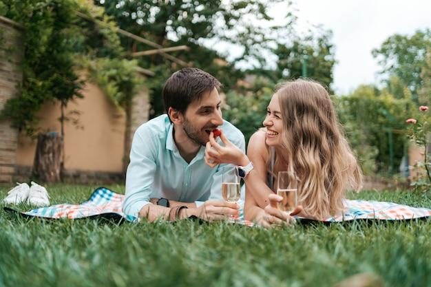 Vacances d'été, gens, romance, homme et femme se nourrissant de fraises tout en buvant du mousseux et en profitant du temps ensemble à la maison