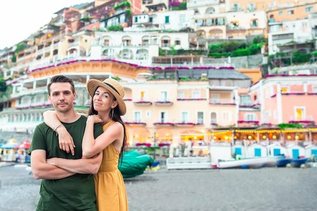 Vacances d'été en italie. jeune couple dans le village de positano sur le fond, côte amalfitaine, italie