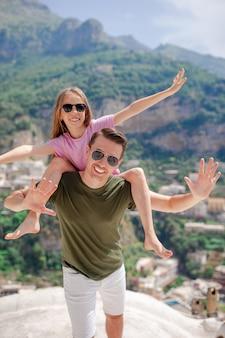 Vacances d'été en italie, jeune homme et enfant dans le village de positano sur le fond, côte amalfitaine, italie