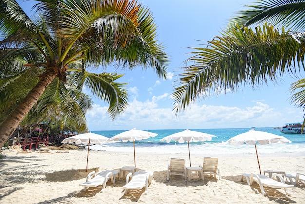 Vacances d'été nature voyage beau paysage d'été avec chaise parasol sur le sable - vacances tropicales feuille de cocotier palmier sur la plage avec la lumière du soleil sur le ciel bleu mer et océan