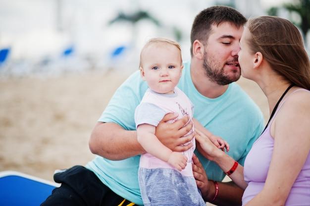Vacances d'été. parents et personnes activité de plein air avec les enfants. bonnes vacances en famille. père, mère enceinte, petite fille assise sur un transat à la plage de sable de la mer.