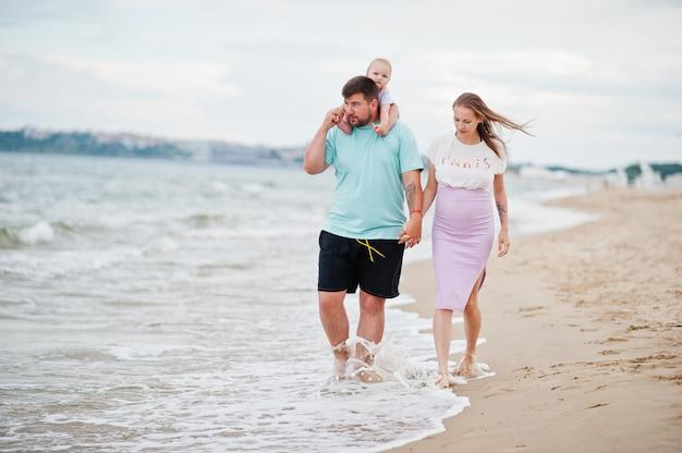 Vacances d'été. parents et personnes activité de plein air avec les enfants. bonnes vacances en famille. père, mère enceinte, petite fille sur la plage de sable de la mer.