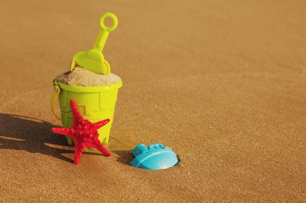 Vacances d'été. seau et bêche sur une plage de sable fin.