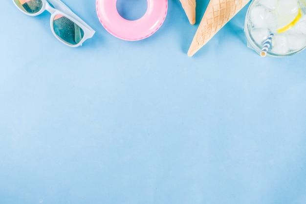 Vacances d'été vacances concept fond chapeau lunettes de soleil boisson rafraîchissante (limonade mojito) avec glace cornet de crème glacée bouée de sauvetage fond bleu flatlay ci-dessus