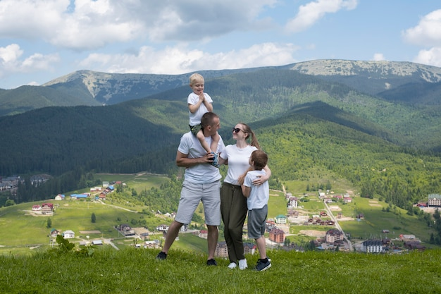Vacances en famille. les parents et les deux fils admirent la vue sur la vallée. montagnes au loin. vue arrière