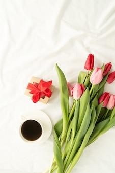 Vacances et fête. vue de dessus des tulipes roses, tasse à café et boîte-cadeau sur lit blanc, pose à plat