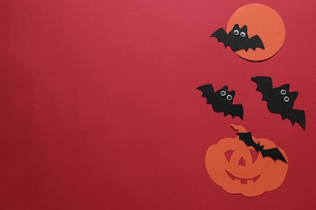 Vacances d'halloween. composition avec diverses figurines en papier d'halloween. vue d'en-haut. sur fond rouge