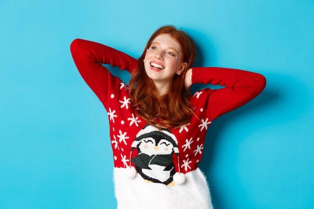 Vacances d'hiver et concept de célébration. adolescente détendue tenant les mains derrière la tête et regardant à gauche la promo, se reposant la veille de noël, debout sur fond bleu.