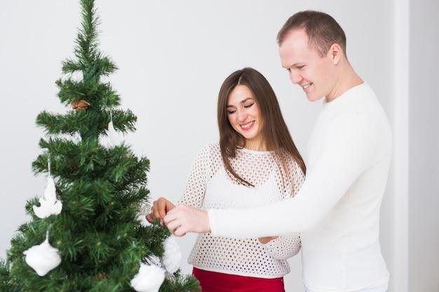 Vacances d'hiver et concept de personnes - couple d'amoureux accrochant des décorations sur un arbre de noël.