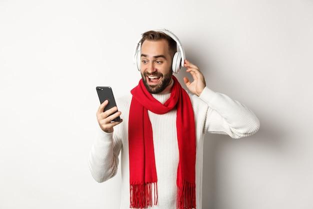 Vacances d'hiver et concept technologique. heureux homme écoutant de la musique dans des écouteurs, regardant émerveillé par l'écran du mobile, debout sur fond blanc.