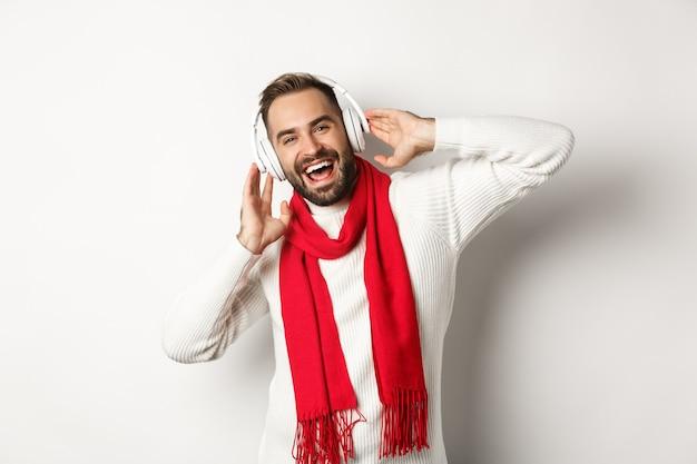 Vacances d'hiver et concept technologique. heureux homme souriant, écoutant de la musique dans les écouteurs, portant une écharpe avec un pull, fond blanc