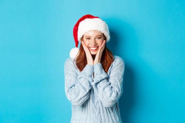 Vacances d'hiver et concept de la veille de noël. fille rousse joyeuse en bonnet de noel, célébrant le nouvel an, rougissant et souriant heureux, debout sur fond bleu.