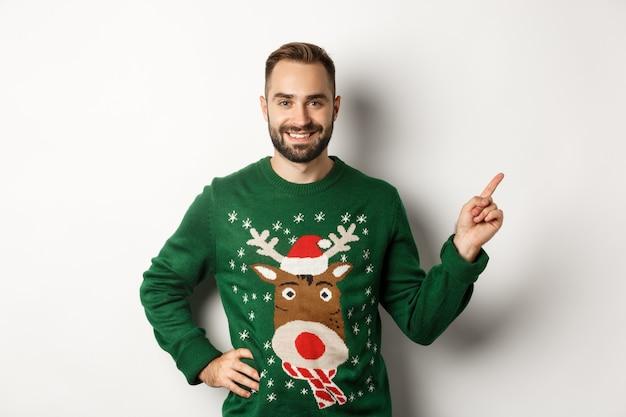 Vacances d'hiver et noël. bel homme adulte barbu pointant le doigt vers la bannière promotionnelle, debout dans un pull drôle sur fond blanc