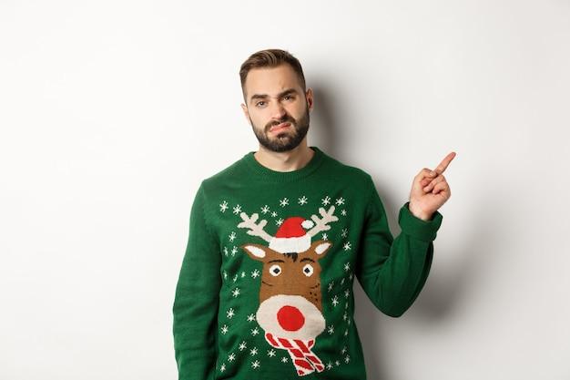 Vacances d'hiver et noël. mec mécontent et grincheux se plaignant, portant un pull drôle, pointant le doigt sur la promo du coin supérieur droit, fond blanc.