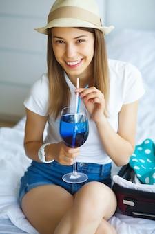 Vacances. jeune belle fille assise sur le lit habillée d'un chapeau