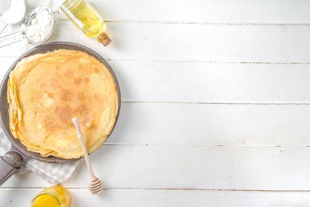 Vacances maslenitsa traditionnelles d'europe de l'est. cuisson des crêpes crêpes, avec des ingrédients, du miel et des fruits frais