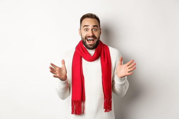 Vacances de noël et concept de célébration. mec barbu semblant surpris par les offres promotionnelles du nouvel an, haletant étonné, portant une écharpe et un pull rouges, fond blanc.
