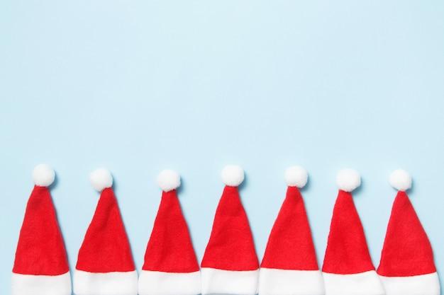 Vacances de noël et du nouvel an. chapeaux de père noël sur un bleu