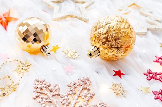 Vacances de noël et du nouvel an avec des décorations et des ampoules. boules brillantes dorées, flocons de neige et confettis étoiles.