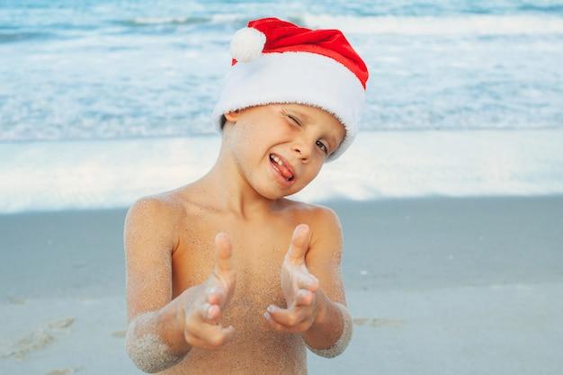 Vacances de noël sur l'île tropicale. heureux garçon posant en bonnet de noel sur la plage.