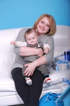 Vacances de noël. jeune grand-mère avec son petit-fils sur un canapé blanc près de l'arbre de noël. mur bleu avec une lune blanche et des étoiles sur un mur.
