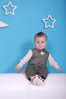 Vacances de noël. mignon petit garçon sur un canapé blanc. mur bleu avec une lune blanche et des étoiles sur un mur.