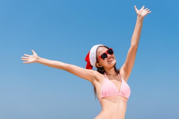 Vacances de noël vacances amusantes de plage bikini femme asiatique courir insouciant des éclaboussures d'eau profitant de la liberté de nager escapade de paradis de voyage des caraïbes avec noël santa hat. modèle de corps sexy.